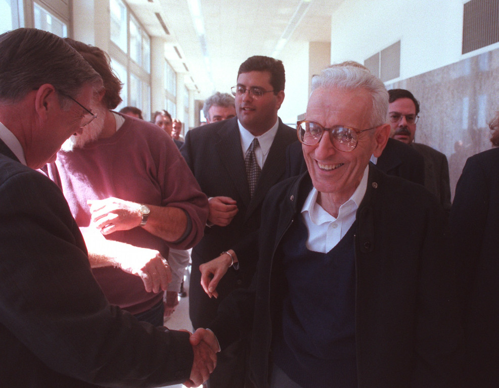 Description of . Dr. Jack Kevorkian is greeted by a well-wisher in the hallway before heading into court for his sentencing in his murder trial of Thomas Youk at Oakland County Circuit Court. Judge Jessica Cooper sentenced Kevorkian to 10-25 years and refused to grant any bond.