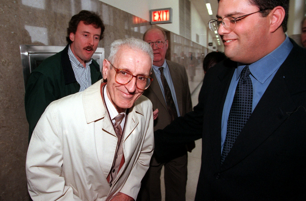 Description of . Doctor Jack Kevorkian, left, accompanied with his attorney David Gorosh leaves the Oakland County courthouse after his arraignment before judge Jessica Cooper.