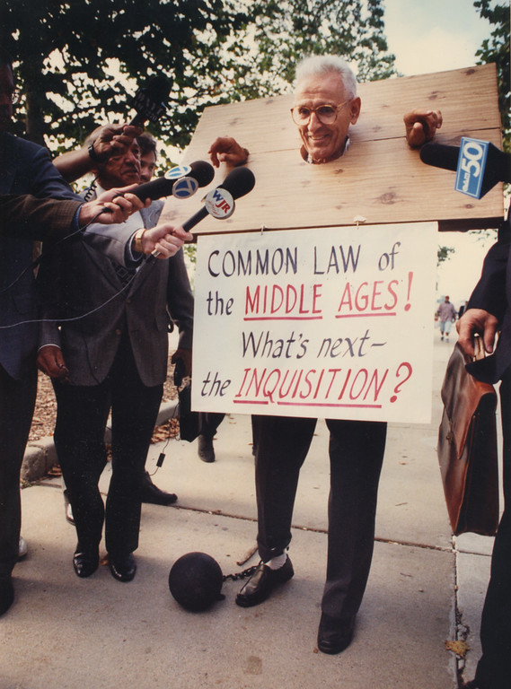 Description of . 9/14/1995- Dr. Kevorkian with pillory and ball & chain outside Oakland County courthouse.