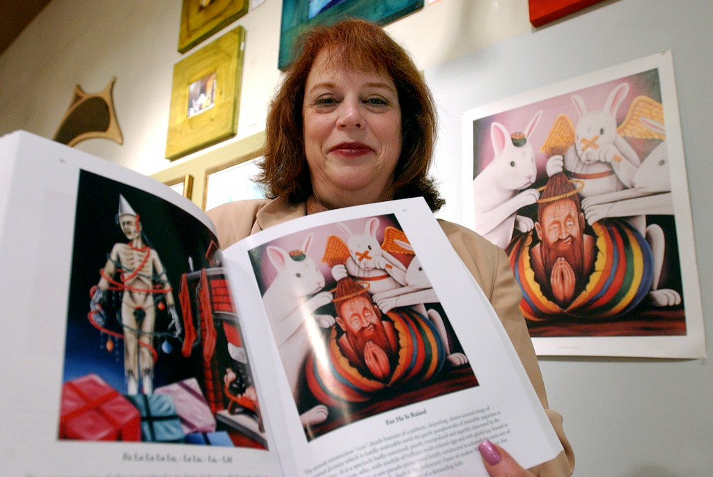 Description of . Anne Kuffler, owner of Ariana Gallery in downtown Royal Oak displays the newly released book titled Glimmer IQs by Dr. Jack Kevorkian that will be sold exculsivly at her gallery. A print titled For He Is Raised by Dr. Kevorkian hangs in the gallery,  which is featured in his book along with many other works he painted.