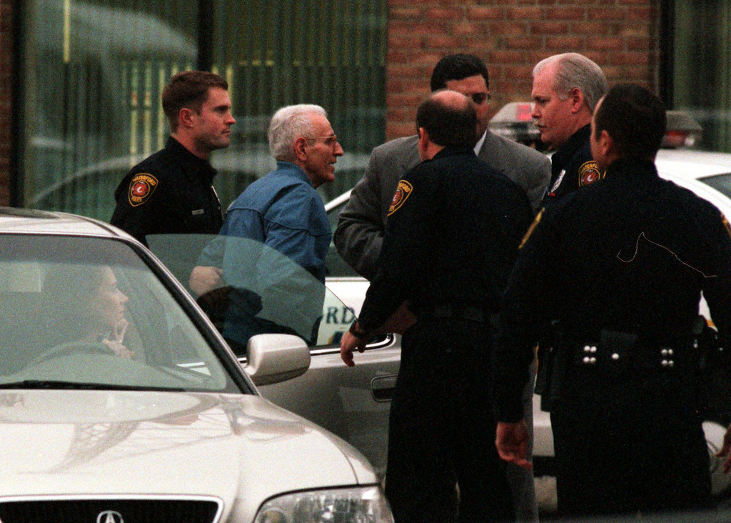 Description of . Jack Kevorkian is escorted to the police station in Waterford Township by police officers for his arraignment Wednesday after turning himself in.