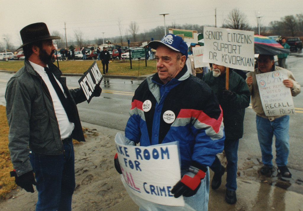 Description of . 12/2/1993- Mark Cushman, left, a one-man crusade against the Friends Of Dr. Kevorkian at the Oakland County jail.