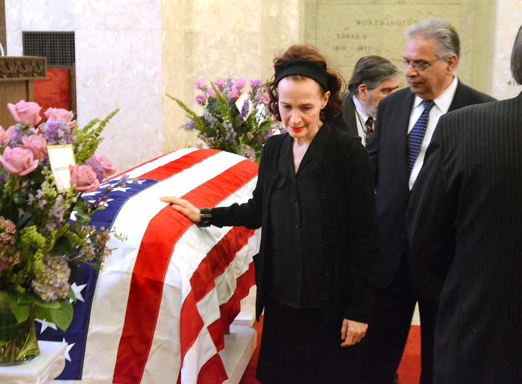 Description of . ***WITH VIDEO*** Avan Janus, niece of Dr. Jack Kevorkian, puts her hand on his casket after the memorial service for him at White Chapel Cemetery in Troy.  The Oakland Press/TIM THOMPSON