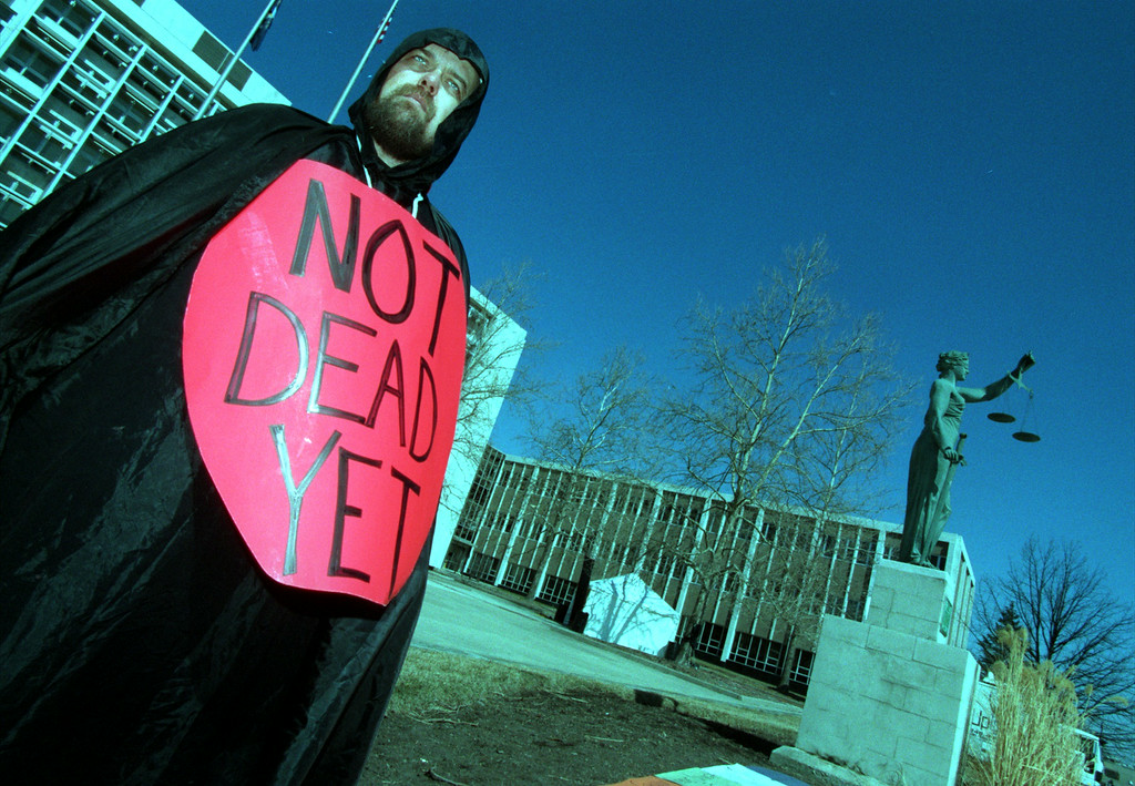 Description of . Ron Ford dressed as the grim reaper representing the Not Deads Yet group stands outside the Oakland County Courthouse during the Jack Kevorkian murder trail.