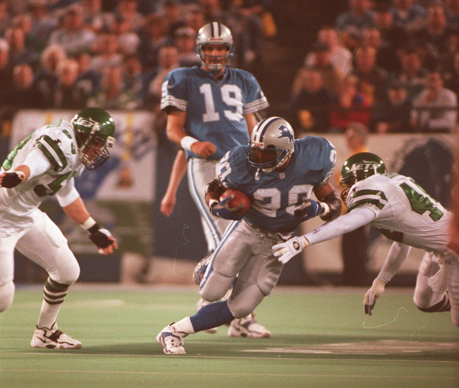 Description of . Lion Barry Sanders splits two NY Jets in the 2nd quarter at the Silverdome. Sanders is trying to finish with over 2000 yards and a win puts the Lions in the playoffs.