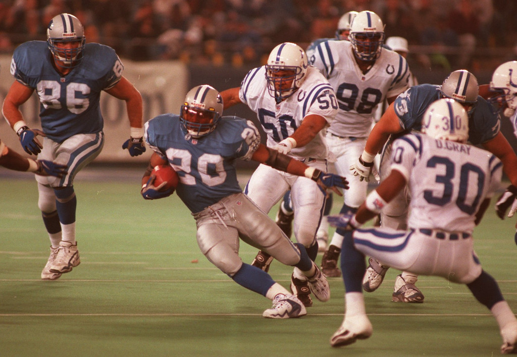 Description of . Detroit Lions Barry Sanders (20) blows by Elijah Alexander (50) and Derwin  Gary both of the Indianapolis Colts during Sunday's game played at  the Pontiac Silverdome. Detroit won 32-10 over the Colts.