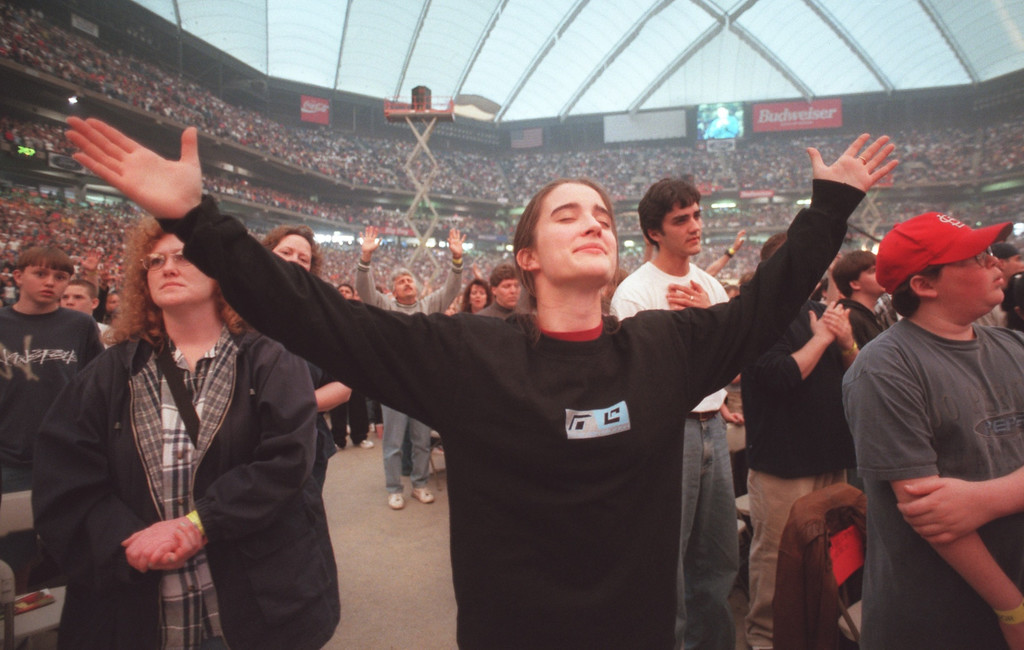Description of . Emily Tiley , 15 , of Detroit, prays during a song  at the 'Acquire the Fire's Day One' at the Pontiac Silverdome. The event brought thousands of teens to pray , sing and listen to inspirational speeches at the Silverdome Friday evening through the Teen Mania Ministries. The event runs throughout the weekend.  (The Oakland Press /Amy E. Powers)
