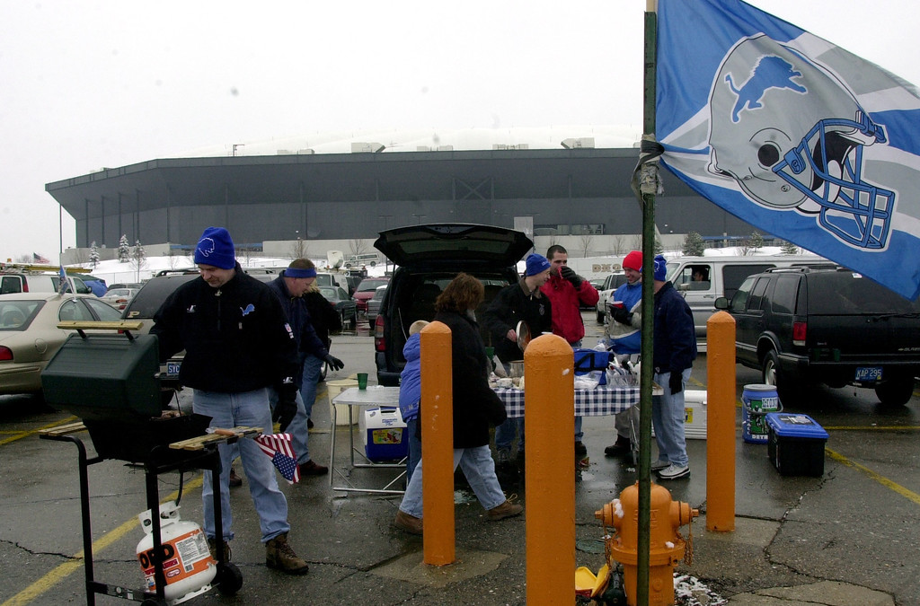 Description of . Bill Klotz, far left, of Troy tailgate with friends and family in the parking lot of the Pontiac Silverdome prior to the start of Sunday's game against the Dallas Cowboys at the Pontiac Silverdome. The Lions won 15-10 over Dallas to end the season and their final game played at the Silverdome.