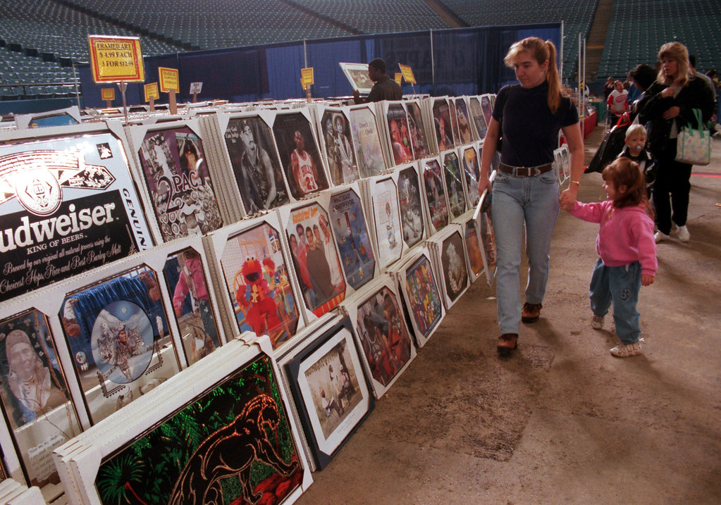 Description of . Wendy Cole and her daughter, Kayla, 3, of Auburn Hills, look over the framed art at the Sale of the $entury at the Pontiac Silverdome Saturday.