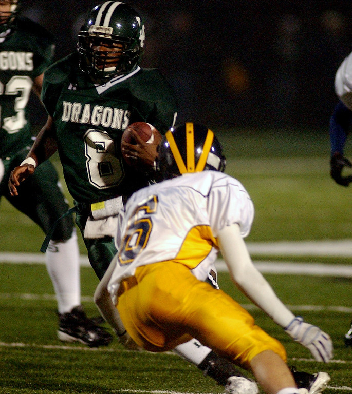 Description of . Lake Orion High School football player Mikael Lott, left, runs for yardage as he is about to be tackled by Clarkston defender Andrew Schram during second quarter action, Friday, October 24 2008, at Lake Orion HS in Lake Orion, Mich.  (The Oakland Press/Jose Juarez)