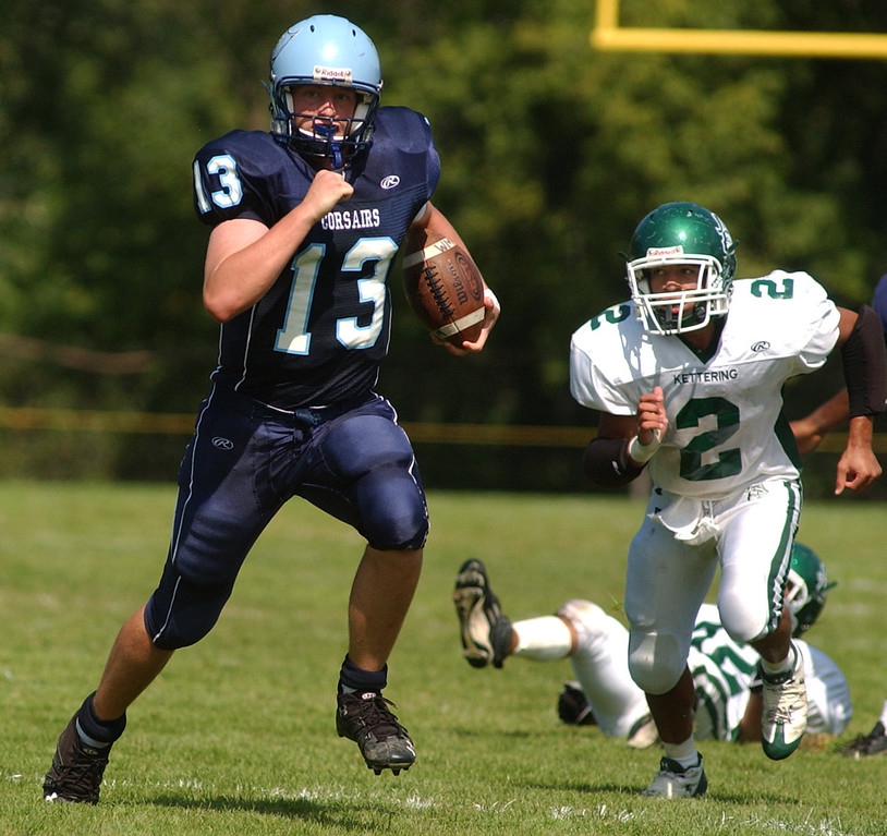 Description of . Waterford Mott High School football quarterback Tyler Bush, left, scrambles for yardage, as he is chased by Waterford Kettering defender Chris Smith, during first quarter action, Saturday, September 20, 2008, in a game played at Mott HS in Waterford, Mich.  (The Oakland Press/Jose Juarez)