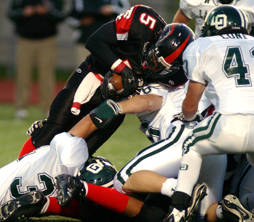 Description of . Troy High School football player Damon Brown, standing left, is tackled by a swarm of Lake Orion defenders during first quarter action, Friday, October 3, 2008, at Troy HS in Troy, Mich.  (The Oakland Press/Jose Juarez)