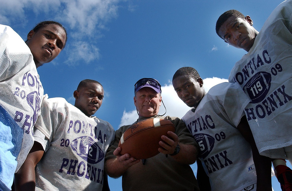 Description of . (from left) Pontiac High School football players Andre Foster, Jabari Martin head coach Greg Garfield, Reggie Washington and Dominique Shaw.