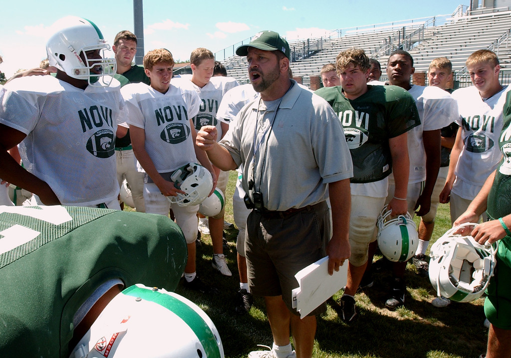 Description of . Novi High School football head coach Tab Kellepourey, middle, yells instructions on several things that he felt the team had to improve on during practice, Tuesday, August 15, 2006, at Novi HS in Novi, Mich.  (The Oakland Press/Jose Juarez)