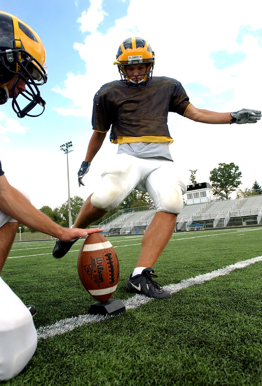 Description of . Clarkston High School football kicker Ryan Breen, right, practices kicking extra points as the ball is held by teammate Eric Ogg.  Photo taken during practice, Tuesday, August 22, 2006, at Clarkston HS in Clarkston, Mich.  (The Oakland Press/Jose Juarez)