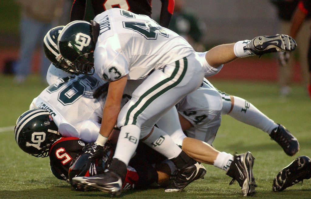 Description of . Troy High School football player Damon Brown, bottom, is tackled by a swarm of Lake Orion defenders during first quarter action, Friday, October 3, 2008, at Troy HS in Troy, Mich.  (The Oakland Press/Jose Juarez)