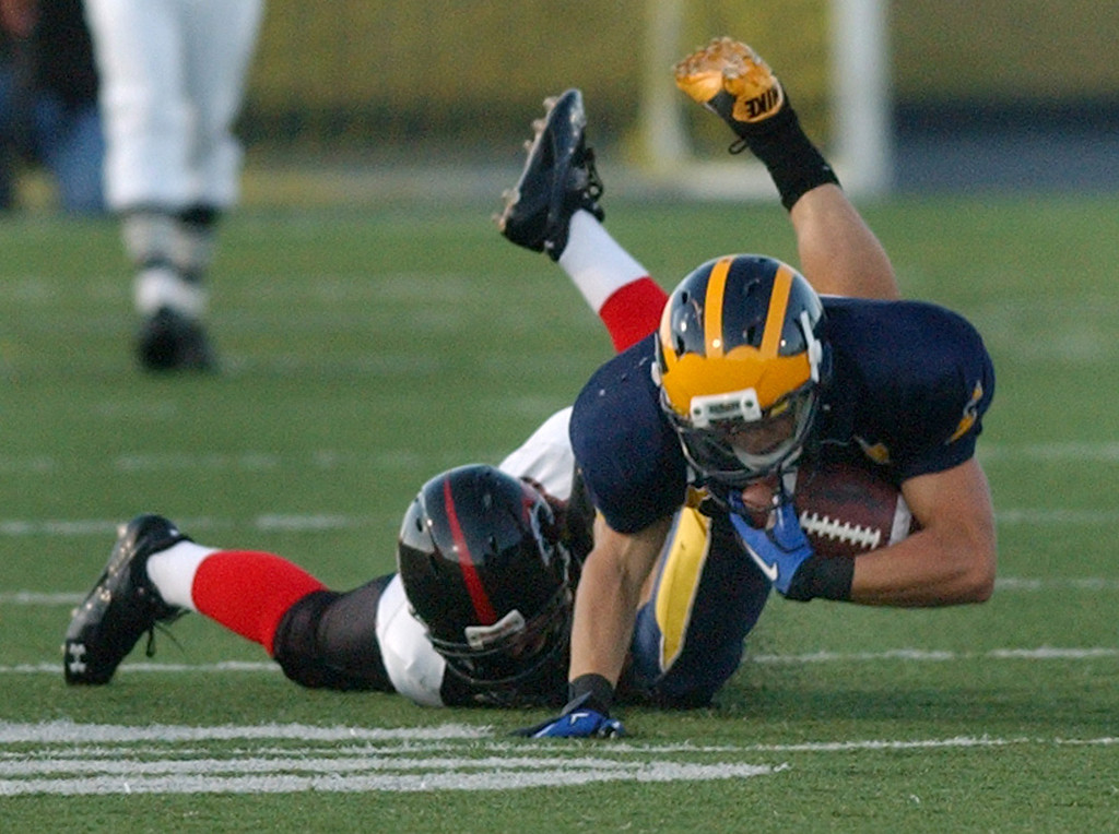 Description of . Clarkston High School football player Joey Goss, front, dives for yardage, as he is tackled by Troy defender Matt Oppenlander in the second quarter.  Photo taken on Friday, September 17, 2010, in a game played at Clarkston HS in Clarkston, Mich.  (The Oakland Press/Jose Juarez)