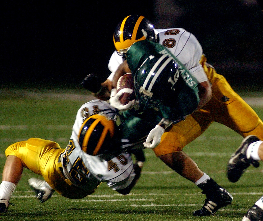 Description of . Lake Orion High School football player Marques, middle, runs for yardage and is tackled by Clarkston defenders Alex Popp, bottom, and Adam Koelb during first quarter action, Friday, October 24 2008, at Lake Orion HS in Lake Orion, Mich.  (The Oakland Press/Jose Juarez)