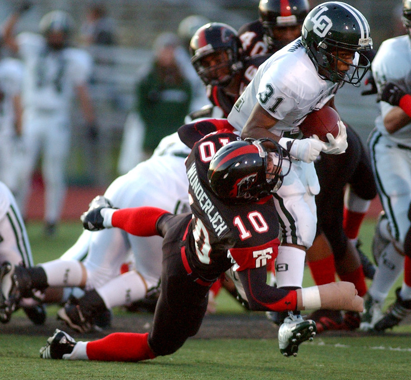 Description of . Lake Orion High School football player Marques Stevenson, top, runs over Troy defender Robert Wunderlich, during first quarter action, Friday, October 3, 2008, at Troy HS in Troy, Mich.  (The Oakland Press/Jose Juarez)