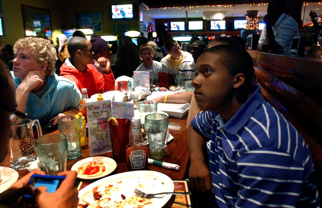 Description of . Tevin Gripper, right, who is a sophomore football player at West Bloomfield High School, watches a Michigan high school football pairings show with his teammates at The Lodge, Sunday, October 26, 2008, in Keego Harbor, Mich.  (The Oakland Press/Jose Juarez)