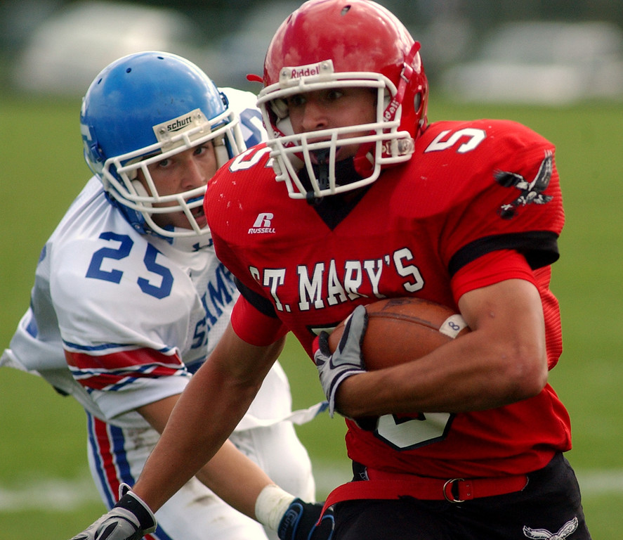 Description of . Orchard Lake St. Mary's High School football player Sam Fioroni, front, runs for yardage as he is chased by Catholic Central defender John Jakubik during first quarter action, Saturday, October 4, 2008, at OLSM HS in Orchard Lake, Mich.  (The Oakand Press/Jose Juarez)