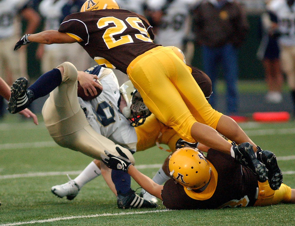 Description of . Stoney Creek High School football running back Danny Cobb (bottom left) is swarmed by several Rochester Adams defenders in the first quarter, Friday, September 5, 2008, in a game played at Adams HS in Rochester Hills, Mich.  (The Oakland Press/Jose Juarez)