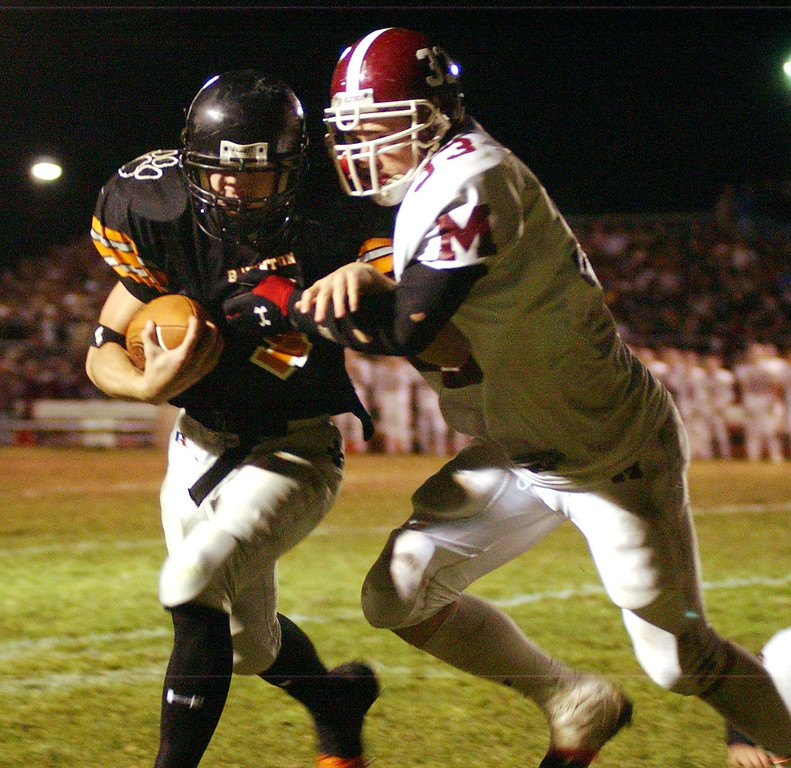 Description of . Milford High School football player Michael Petrucci (right, #33) tackles Brighton player Tony Bravata (#4) during third quarter action, Friday, November 11, 2005, at Brighton HS in Brighton, Mich.