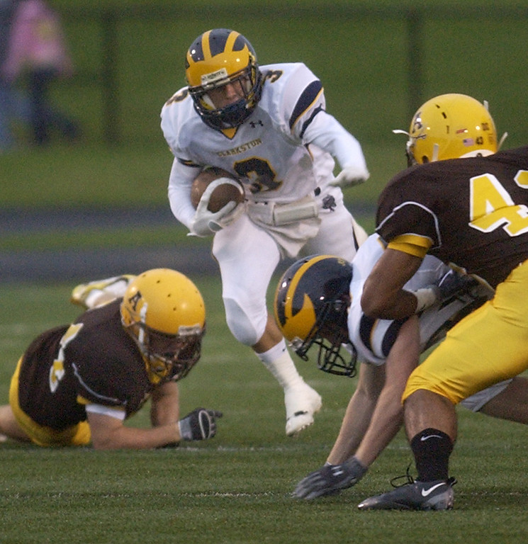 Description of . Clarkston High School football player P.J. Lannon rushes yardage against Rochester Adams during first quarter action, Friday, August 28, 2009, in Rochester Hills, Mich.  (The Oakland Press/Jose Juarez)
