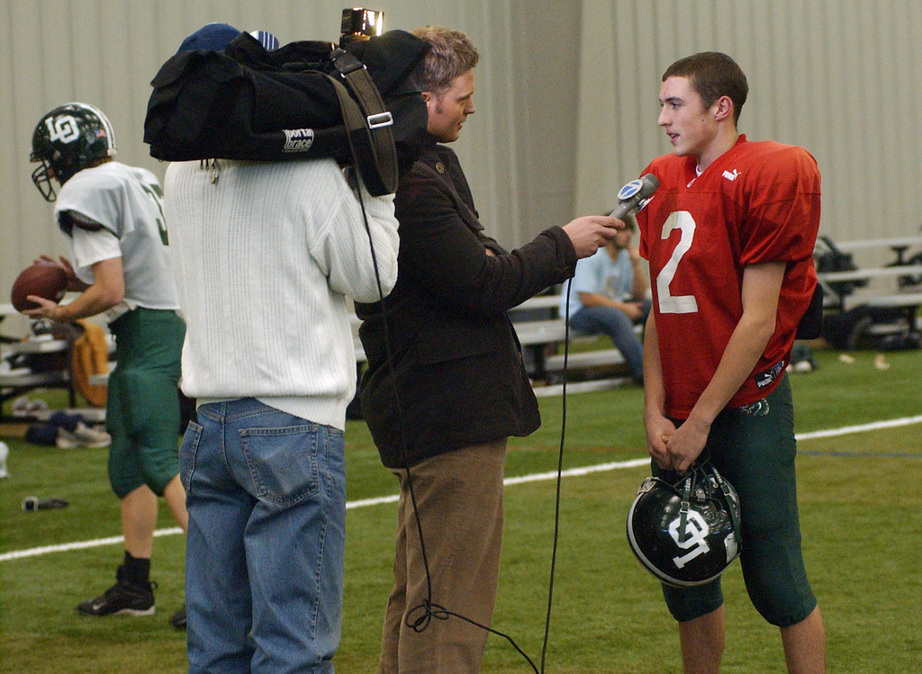Description of . Lake Orion High School football quarterback Sean Charette is interviewed by a local tv station before the start of practice.  Photo taken on Tuesday, November 25, 2008, in Pontiac, Mich.  (The Oakland Press/Jose Juarez)