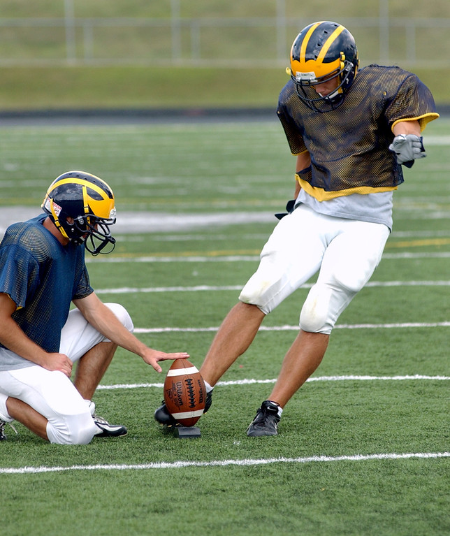 Description of . Clarkston High School football kicker Ryan Breen, right, practices kicking field goals as the ball is held by teammate Eric Ogg.  Photo taken during practice, Tuesday, August 22, 2006, at Clarkston HS in Clarkston, Mich.  (The Oakland Press/Jose Juarez)