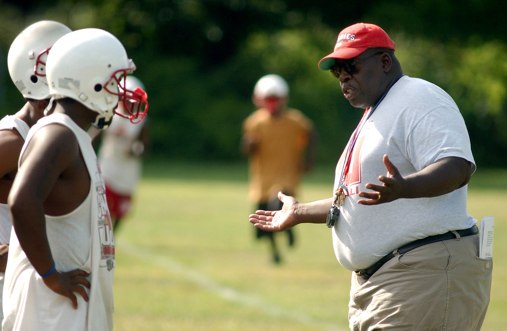 Description of . Pontiac Northern High School football head coach Keith Stephens, far right, chats with two of his players at the start of team practice, Tuesday, August 8, 2006, at Northern HS in Pontiac, Mich.  (The Oakland Press/Jose Juarez)