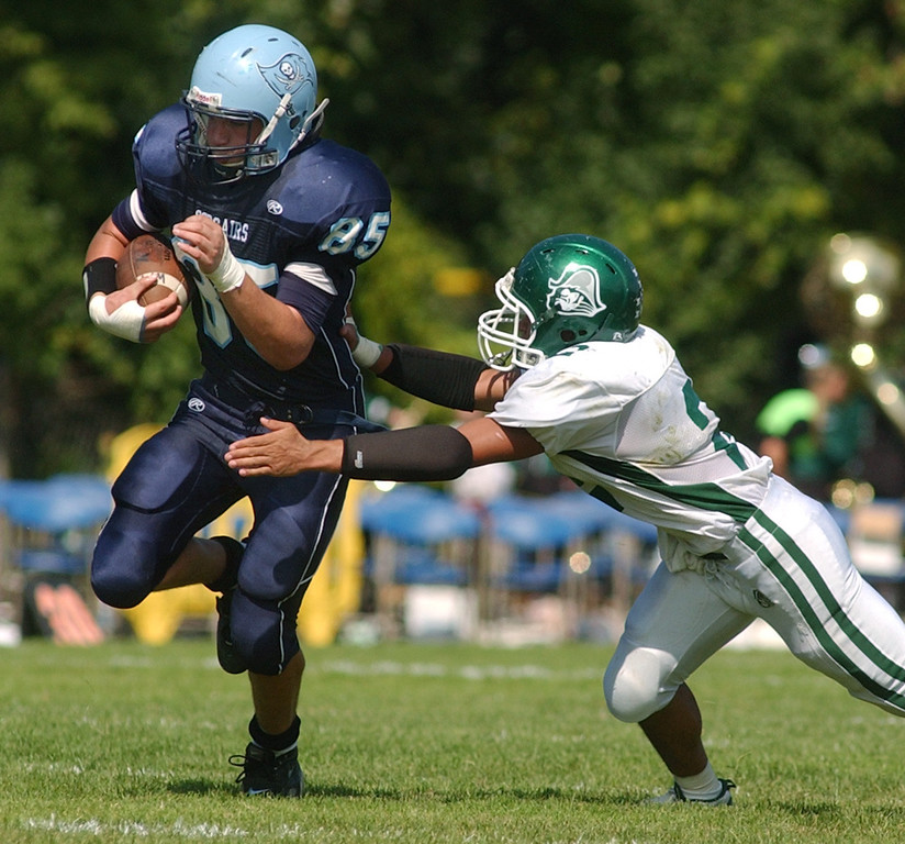 Description of . Waterford Mott High School football player Jacob Wardach, left, runs for yardage as he is chased by an unidentified Waterford Kettering defender during second quarter action, Saturday, September 20, 2008, in a game played at Mott HS in Waterford, Mich.  (The Oakland Press/Jose Juarez)