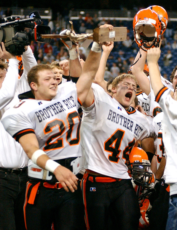 Description of . Birmingham Brother Rice High School football players Mike Radlick (front left, #20) and Matt Pickens (#44) hoist their Division 2 championship trophy after beating Hudsonville, 14-7, Friday, November 25, 2005, at Ford Field in Detroit, Mich.