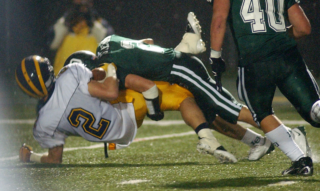 Description of . Lake Orion High School football player Charles Fleck, top, drops Clarkston player Dakota Bender for a loss of yardage in their backfield during second quarter action, Friday, October 24 2008, at Lake Orion HS in Lake Orion, Mich.  (The Oakland Press/Jose Juarez)