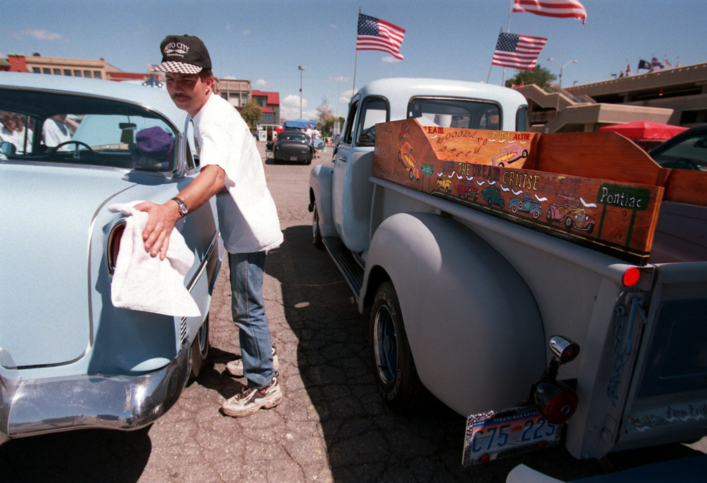 Description of . Bill Teeple, of Pontiac, polishes his 4 door \'55 Chevy in the parking lot outside the Phoenix Center Friday afternoon.   It\'s the third year he\'s participating in the Dream Cruise, but the first year with this car.  Next to him is a \'54 GMC pickup truck, owned by Bob Whitney of Pontiac.