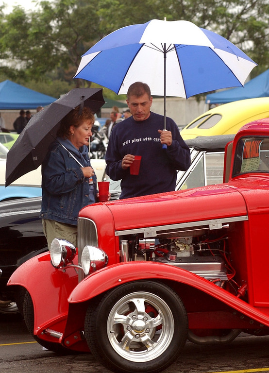 Description of . Chris Napper,right, of Sterling Heights with his freidn Karen Kailer of Chicago checkout a classic 1932 3-window Ford Coup on display in the parking lot of the Phoneix Plaza in downtown Pontiac during Friday night\'s Woodward Dream Cruise. The annual classic cruise goes from Pontiac to Ferndale covering 16-miles of classic cars, food & entertainment along the way.