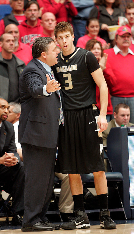 Description of . Oakland's head coach Greg Kampe talks to Travis Bader (3) about his playing during the first half of an NCAA college basketball game against Arizona at McKale Center in Tucson, Ariz., Tuesday, Dec. 20, 2011. (AP Photo/John Miller)