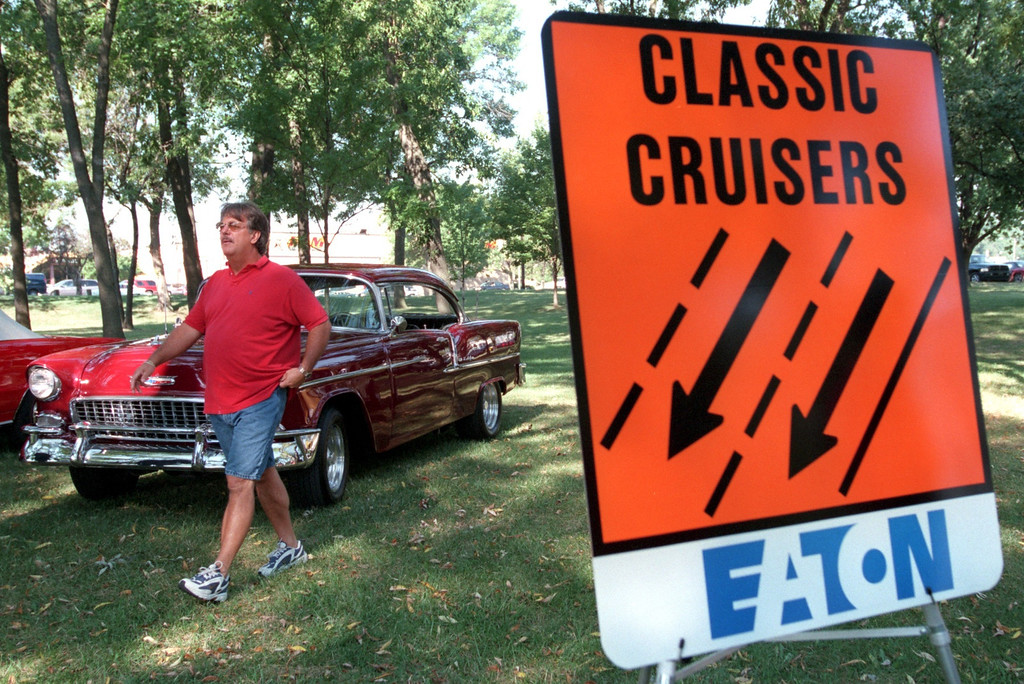 . Classic Cruiser Mike Taylor walks past his red 1955 Chevy Bel-Air during a press conference yesterday in Royal Oak\'s Memorial Park to introduce Dream Cruise lane signs like the one at right, which signals classic cars, as opposed to thru traffic.