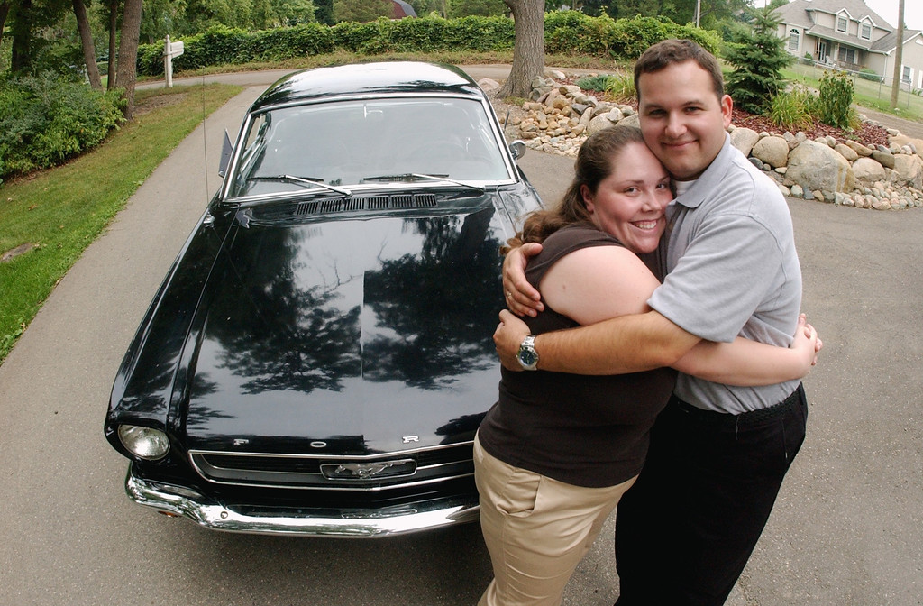 Description of . Michelle Barnett, left, hugs her fiance, Bryan Crandall, in front of Bryan's father's 1966 Mustang, which they will drive after their wedding on Saturday, along the Dream Cruise route.  Photo taken on Thursday, August 18, 2005, in Waterford, Mich.