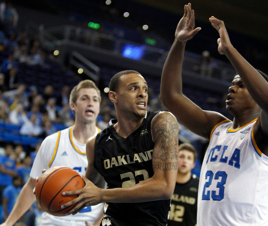Description of . Oakland forward Tommie McCune, center, looks to pass the ball off with UCLA center Tony Parker, right, and forward David Wear, left, defending in the first half of an NCAA college basketball game Tuesday, Nov. 12, 2013, in Los Angeles. (AP Photo/Alex Gallardo)