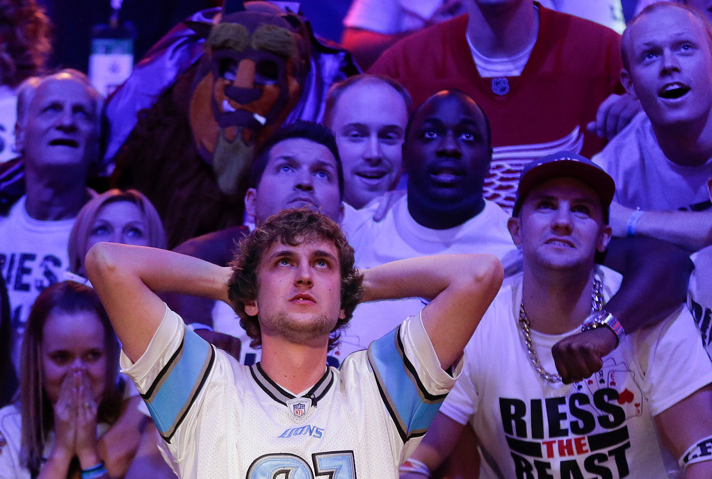 Description of . Ryan Riess watches the flop with supporters after an all-in call by Jay Farber during the World Series of Poker final table, Tuesday, Nov. 5, 2013, in Las Vegas. Farber won the hand to stay alive in the event. (AP Photo/Julie Jacobson)
