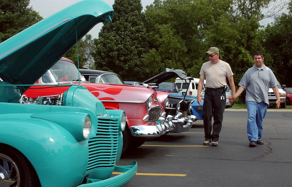 Description of . Dennis McElhone of Howell assits Jeff Jonna of Farmington Hills as they walk around looking at classic car's during the 8th Annual Kennedy Dream Cruise in Pontiac. The event includes classic cars for special needs students in the area.
