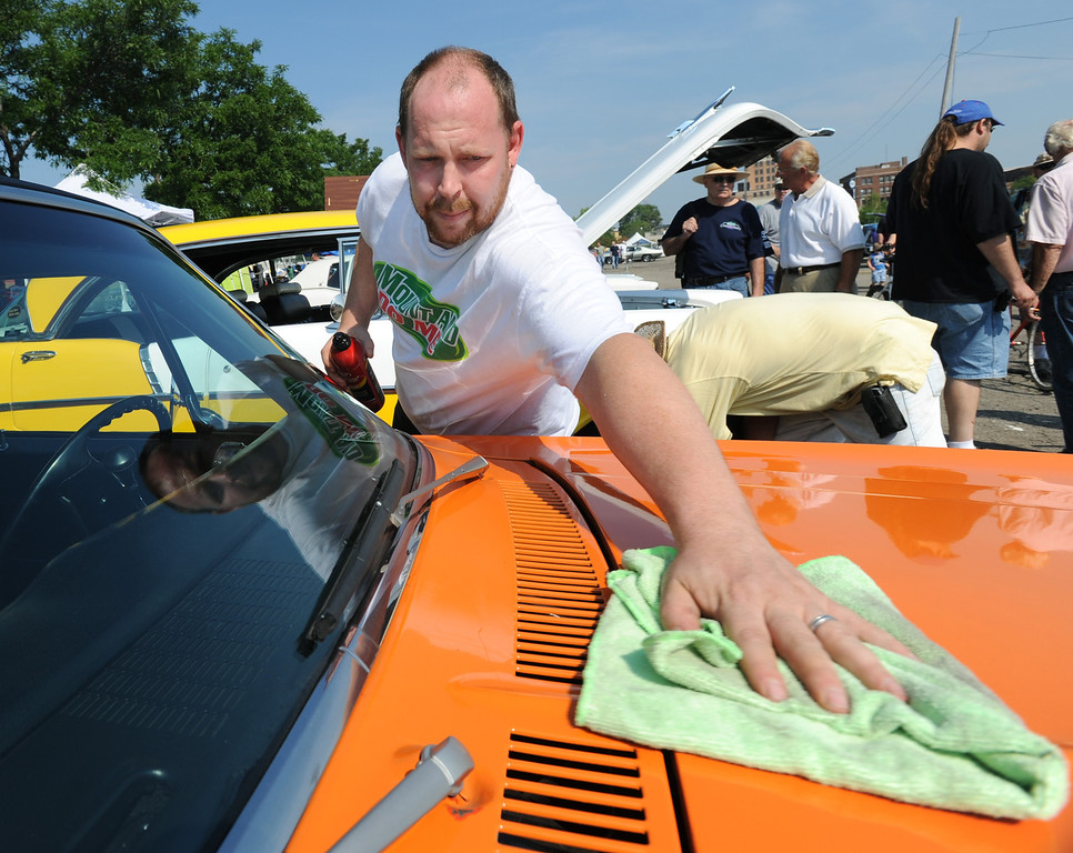 Description of . John Vanderpool of Pontiac, Mich., shines his 1972 Chevy Nova in Lot 9, Saturday, August 15, 2009, in Pontiac, Mich.  (The Oakland Press/Jose Juarez)