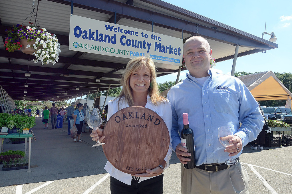 Description of . Marie Hauswirth, (left) Executive Director of the Waterford Area Chamber of Commerce and Jeremy Brown, Oakland County Farmers Market manager, will take part in the Oakland Uncorked wine & food tasting experience August 2nd, pictured Thursday July 25, 2013. (Oakland Press Photo:Vaughn Gurganian)