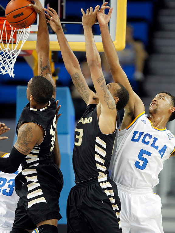 Description of . Oakland guard Duke Mondy, left and forward Tommie McCune, center, compete for a rebound with UCLA guard Kyle Anderson (5) in the first half of an NCAA college basketball game Tuesday, Nov. 12, 2013, in Los Angeles. (AP Photo/Alex Gallardo)