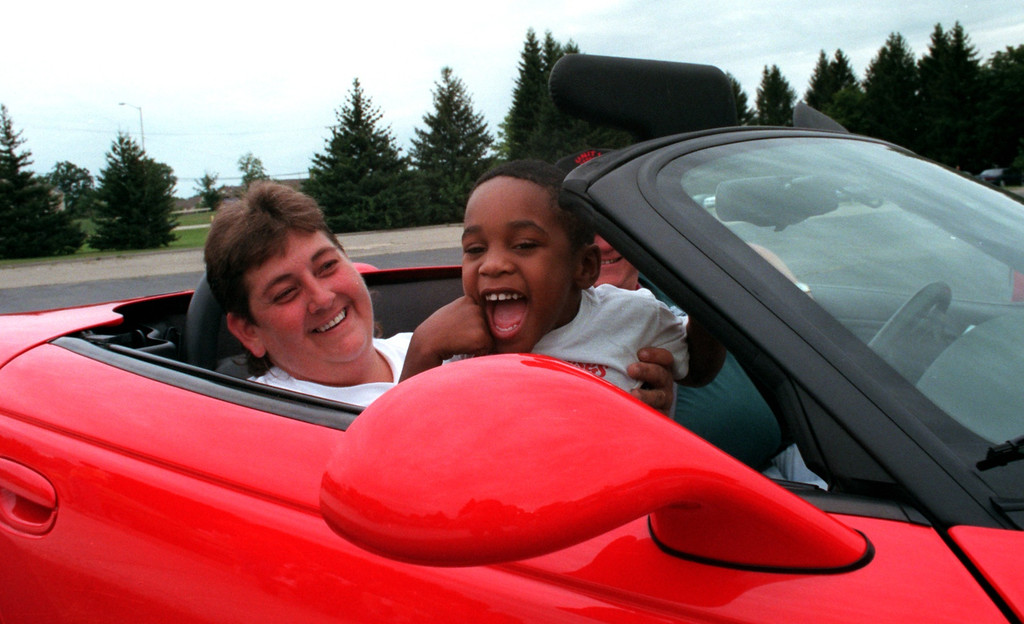 Description of . Marcus Redmond,4, (right) of Pontiac sits with Jeannette Perry, an instructor at Kennedy, as he cruises around the parking lot in a new Plymouth Prowler at the Kennedy Dream Cruise.  The kids from the center were given the opportunity to take rides in three different cars around the parking lot following a 50s and 60s dance at the Kennedy Center.