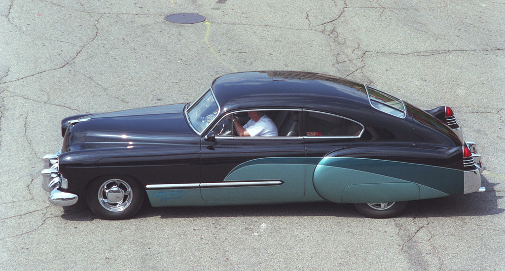 Description of . Classic 1948 Cadillac cruises into downtown Pontiac  Friday afternoon as people arrive for the Dream Cruise. (Photog found out later this is Oakland Press\' own Ed Noble-)