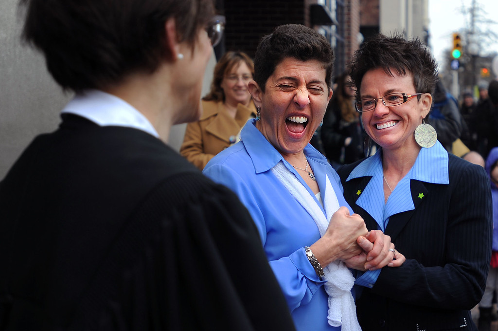 Description of . Lisa Ruby and Lisa Cavico celebrate as they get married after 8 years together outside the Washtenaw County Clerk's office in Ann Arbor, Mich., Saturday, March 22, 2014, the day after a federal court struck down Michigan's ban on gay marriage. (AP Photo/The Ann Arbor News, Brianne Bowen)