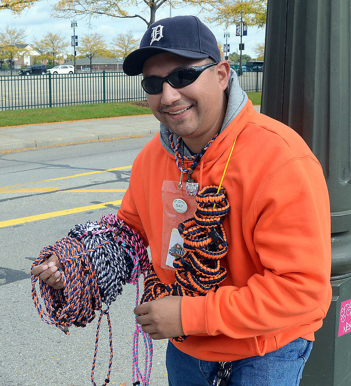 Description of . This street vendor is hoping to sell lots of Tigers necklaces and bracelets at Comerica Park before the start of Game 3 of the ALDS between the Tigers and Oakland A's, Monday October 7, 2013. (Oakland Press Photo:Vaughn Gurganian)
