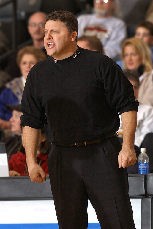 Description of . Oakland University men's basketball head coach Greg Kampe yells instructions to his team during second half action against IUPUI, Saturday, February 8, 2003, at the O'rena on the campus of Oakland University in Rochester Hills, Mich.